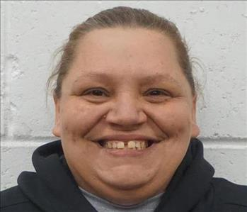 Picture of female employee Chasity Evans in front of white wall.
