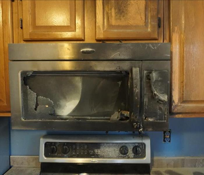 A microwave burnt to a crisp after a stove top fire