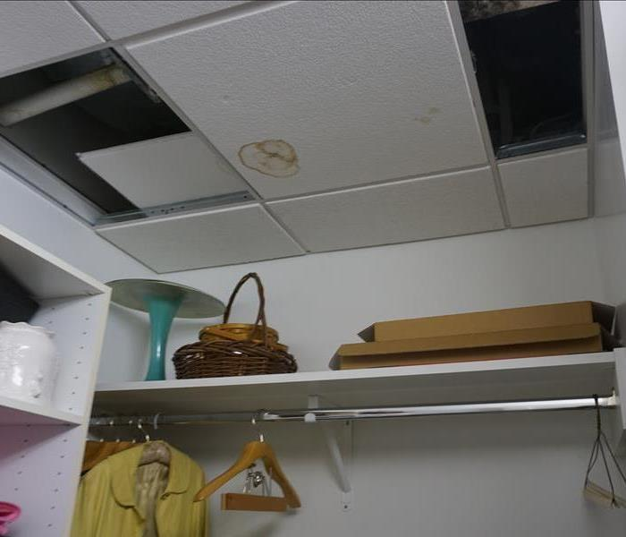 A tile in the closet affected by a water leak above it